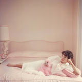 Film star Joan Collins relaxes with her pink poodle on her pink bed. Premium Photographic Print by Slim Aarons