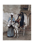 A Man Stands with a Veiled Woman and Child Sitting on a Donkey Photographic Print by Thornton Oakley