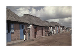 Men Stand by Thatch-Roofed Houses, Alongside a Main Road in Higuey Photographic Print by Jacob J. Gayer