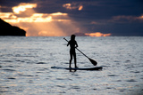 A Young Girl on a Stand Up Paddle Board on Baleia Beach at Sunset Fotografisk tryk af Alex Saberi