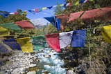 Colorful Prayer Flags Fly over Turquoise Rapids in an Alpine River Photographic Print by Jason Edwards