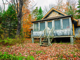 A Cabin in a Forest of Trees in Autumn Hues Photographic Print by Babak Tafreshi