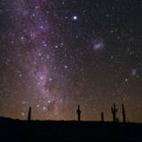 The Southern Sky with Orion, Crux, Sirius, Canopus and Magellanic Clouds over Cacti Photographic Print by Babak Tafreshi
