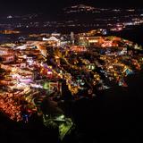 A High Angle Night View of the City Lights of Fira, the Main Town on Santorini Island Photographic Print by Babak Tafreshi