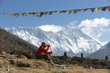A Hiker to Everest Base Camp under a String of Prayer Flags and Everest and Lhotse in the Distance Photographic Print by Alex Treadway