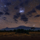 The Magellanic Clouds, Our Neighboring Dwarf Galaxies, Seen Through Clouds over Mount Kilimanjaro Photographic Print by Babak Tafreshi
