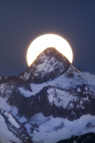 A Super Moon Setting Behind Snow-Dusted Capital Peak Photographic Print by Robbie George
