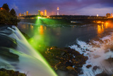 Niagara Falls Illuminated with Colored Lights, and Attractions on the Far Shore at Night Photographic Print by Babak Tafreshi