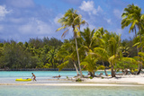 A Man Taking a Kayak Out to Sea from a Tropical Palm Tree-Lined Beach Photographic Print by Mike Theiss