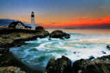The Sun Setting Behind the Portland Head Light as Waves Surge onto the Rocky Shore Photographic Print by Robbie George