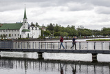 Two People Walk on a Bridge Near the Free Church, or Frikirkjan Photographic Print by Jill Schneider