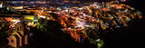 A High Angle Night View of the City Lights of Fira, the Main Town on Santorini Island Photographic Print by Babak Tafreshi
