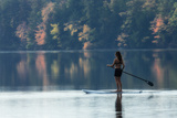 A Woman Paddleboarding in a Calm Pond Rimmed by Trees in Autumn Hues Photographic Print by Robbie George