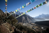 Prayer Flags Flutter in the Wind Above Thame, a Remote Village in the Everest Region of Nepal Photographic Print by Alex Treadway