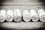 Dated Wine Bottle Corks On The Wooden Background Cartel de plástico por Dasha Petrenko