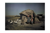 Women Stand in Front of a Primitive Straw Covered Hut Photographic Print by Hans Hildenbrand