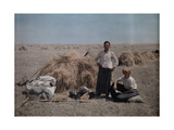 Peasant Couple Work During Harvest, their Belongings Beside Them Photographic Print by Hans Hildenbrand