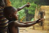 A Bassari Child Holding Out Hands to Collect Rainwater, Bassari Country, East Senegal Papier Photo par Enrique Lopez-Tapia