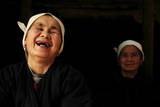 Two Dong Women, One Laughing, in a Dark Room, Sanjiang Dong Village, Guangxi, China Photographic Print by Enrique Lopez-Tapia