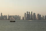 A Traditional Wooden Dhow Boat Sails Past Modern Skyscrapers, West Bay Financial District, Doha Photographic Print by Stuart Forster