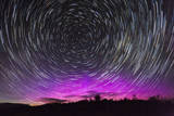 Stars Swirl around Polaris as Northern Lights Dance on the Horizon over Jackson Hole, Wyoming Photographic Print by Mike Cavaroc