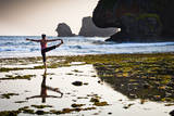 A Young Woman Practices Yoga at Low Tide During a Hazy Sunset at Siung Beach Photographic Print by Dan Holz