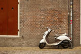 A Scooter Parked on the Sidewalk Outside of Oude Kerk Church in Amsterdam, Netherlands Photographic Print by Carlo Acenas