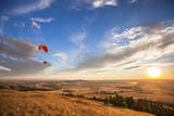 A Male Paraglider Paraglides Above Rolling Farm Lands at Sunset Near Moscow, Idaho Photographic Print by Ben Herndon