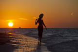 A Silhouette of a Woman Wearing a Hat Walking in the Surf at Sunset on Holbox Island, Mexico Photographic Print by Karine Aigner