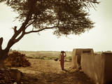 A Rajasthani Woman Carries Her Things on Her Head in a Small Village in Western Rajasthan Photographic Print by D. Scott Clark