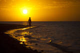 A Silhouette of a Woman Walking in the Waves of the Surf at Sunset in Holbox Island, Mexico Photographic Print by Karine Aigner