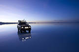 Travelers Drive their Suv across a the Salar De Uyuni, a Flooded Salt Flat, in Bolivia Photographic Print by Sergio Ballivian