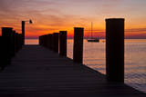 Sunrise on the Water with an Empty Dock and a Sailboat in the Distance of Tilghman Island, Maryland Photographic Print by Karine Aigner