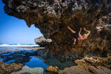 A Young Woman Climbs on a Low-Tide Boulder in Siung Beach Just Outside Yogyakarta, Indonesia Photographic Print by Dan Holz