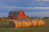 Canada, Alberta, Grande Prairie. Red Barn and Hay Bales at Sunset Photographic Print by  Jaynes Gallery