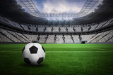 Black and White Leather Football in a Vast Football Stadium with Fans in White Photographic Print by Wavebreak Media Ltd