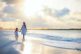 Mother and Her Little Daughter Walking along a Beach on Sunset Photographic Print by BlueOrange Studio