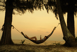 Young Lady Reading the Book in the Hammock on Tropical Beach at Sunset Photographic Print by Dudarev Mikhail