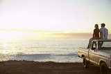 Rear View of Young Couple on Pick-Up Truck Parked in Front of Ocean Enjoying Sunset Posters by  Nosnibor137
