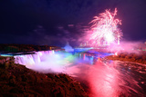 Niagara Falls Lit at Night by Colorful Lights with Fireworks Posters by Songquan Deng