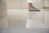 Low Section of Woman Standing on Weighing Scale in Bathroom Photographic Print by  Nosnibor137