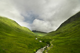River Flowing through a Valley in the Scottish Highlands, the Mountains are Covered in Clouds Photographic Print by  unkreatives