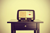 Picture of an Antique Radio Receptor on a Desk, with a Retro Effect Poster by  nito