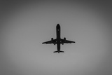 Silhouetted Aircraft Landing Photographic Print by Ingo Jezierski