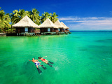 Couple Snorkling in Tropical Lagoon with over Water Bungalows Photographic Print by Martin Valigursky