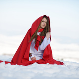 Beautiful Woman with Red Cloak Sitting on the Snow in Winter Photographic Print by  mirceab