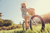 Carefree Woman Riding Bicycle in Park Having Fun on Summer Afternoon Print by  warrengoldswain