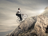 Young Businessman Pedaling a Bicycle on the Rocks Photographic Print by  olly2