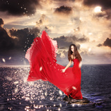 Girl in Red Dress Standing on Ocean Rocks Photographic Print by  Melpomene