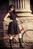 Beautiful Brunette Standing near Her Old Bicycle over City Background. Retro Style. Prints by  prometeus